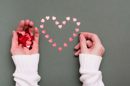 Female hands lay out of small hearts a heart shape on a green background