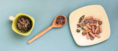 Herbal medicinal capsules, pills and dried oregano in a cup and in a wooden spoon on a green background. Alternative medicine. Web banner