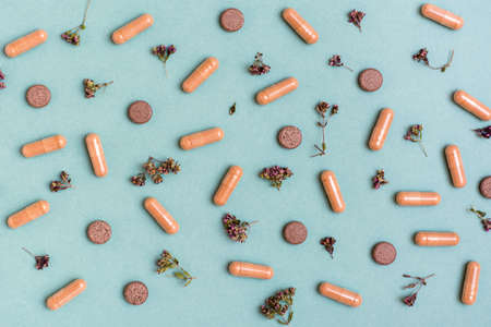 Abstract green background with capsules, pills and herbs. Alternative medicine. Top view Standard-Bild