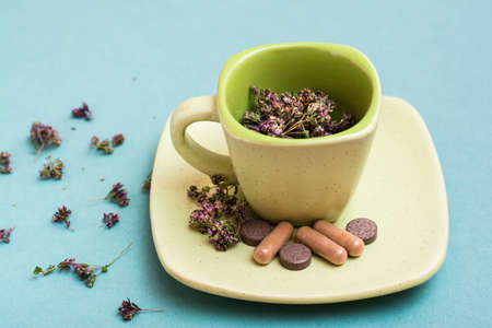 A cup with dried oregano and herbal medicinal capsules and pills on a saucer on a green background. Alternative medicine