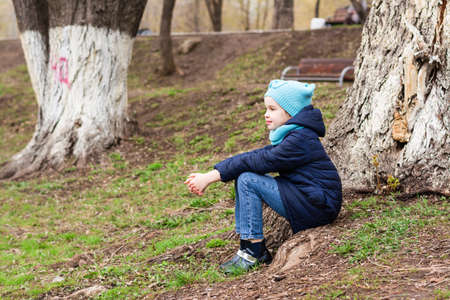 A lonely girl sits in solitude at the root of a tree in the park and looks into the distance. Mental health Standard-Bild
