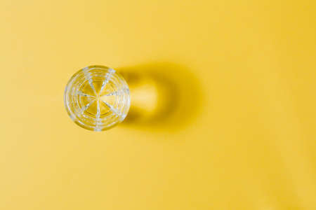 A lonely glass of water in a yellow-gray palette. Loneliness and self-sufficiency concept. Copy space. Top view