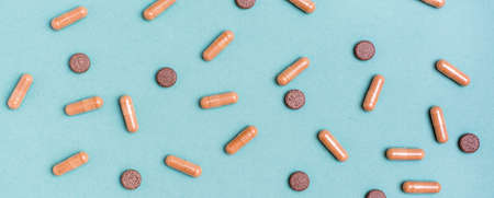 Abstract green background with herb capsules and pills. Alternative medicine. Top view. Web banner