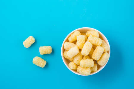 Corn sticks in powdered sugar in a bowl on a blue background. Top view