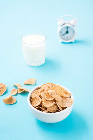 A bowl of cereal, a glass of milk and an alarm clock on a blue background. Scheduled breakfast. Vertical view Standard-Bild