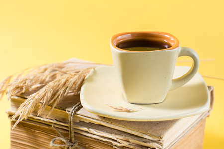 A cup of coffee on old books and dry ears of corn in yellow and harsh light. Wellness, harmony, inclusiveness. Copy space