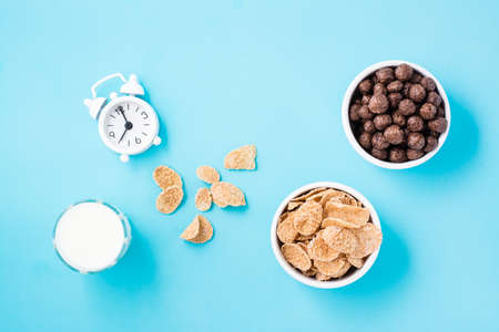 Bowls with cereal flakes and chocolate balls, a glass of milk and an alarm clock on a blue background. Scheduled breakfast, choice of dishes. Top view Standard-Bild