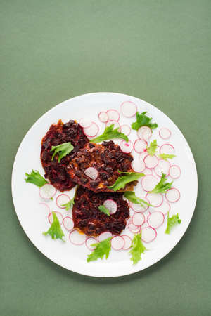 Vegetable diet food. Beetroot steak, radish and frieze salad leaves on a plate on a green background. Vertical view, copy space Standard-Bild
