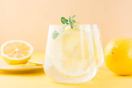 Sparkling water with lemon, melissa and ice in glasses and lemon slices on a saucer on a yellow background. Alcoholic drink hard seltzer. Close-up Standard-Bild