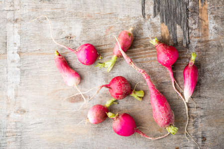 Fresh slightly overgrown radishes on a wooden table. Vegetables for a vegetarian diet. Rustic style. Top view Standard-Bild
