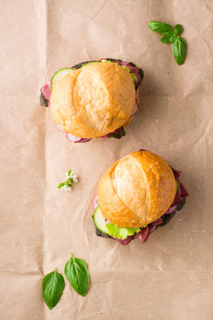 A couple of fresh burgers with pastrami, cucumber, radish and herbs on craft paper. American fast food. Vertical view Standard-Bild