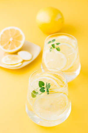 Sparkling water with lemon, melissa and ice in glasses and lemon slices on a saucer on a yellow background. Alcoholic drink hard seltzer. Vertical view