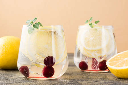 Summer refreshing cold cocktail with lemon and cherry - hard seltzer in glasses on the table. Close-up