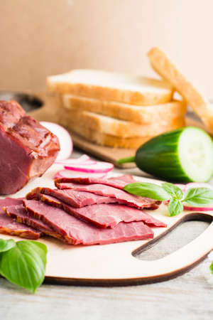 Fresh sliced marbled beef pastrami, cucumber, radish and basil on a cutting board. American delicacy. Rustic style. Vertical view Standard-Bild