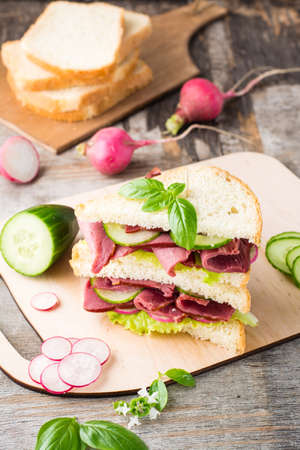 Double sandwich with pastrami and fresh vegetables and herbs on a cutting board. American snack. Rustic style. Vertical view