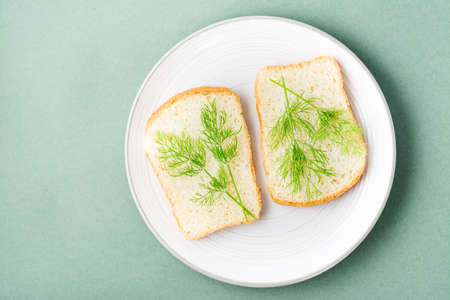 Sandwiches of white bread and fresh dill on a plate on a green background. Vitamin Herbs in a healthy diet. Top view Standard-Bild