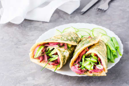 Egg rolls filled with pastrami, vegetables and green onions on a plate on the table. Hearty and high-calorie snack Standard-Bild