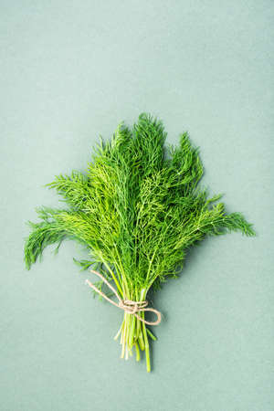 A bunch of fresh dill tied with a rope on a green background. Vitamin greens in a healthy diet. Top and vertical view