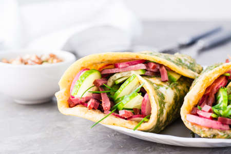 Egg rolls filled with pastrami, vegetables and green onions on a plate on the table. Hearty and high-calorie snack. Close-up