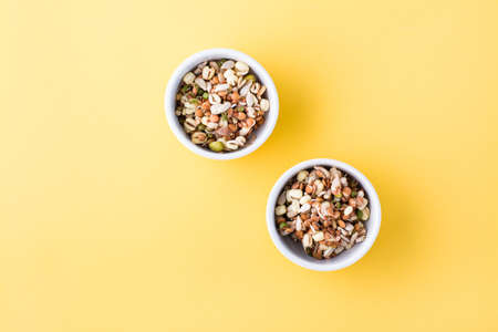 Sprouted grains of mung beans, lentils, flax and sunflowers in bowls on a yellow background. Top view. Copy space