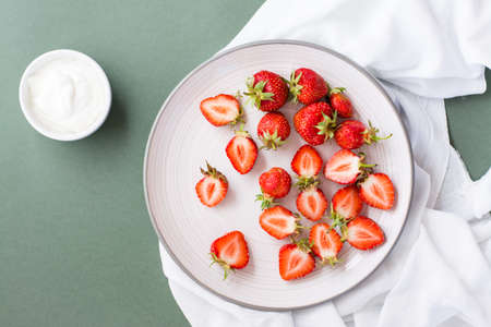 Fresh whole and sliced strawberries on a plate and sour cream in a bowl on a green background. Summer vitamin food. Top view