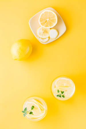 Sparkling water with lemon, melissa and ice in glasses and lemon slices on a saucer on a yellow background. Alcoholic drink hard seltzer. Vertical and top view