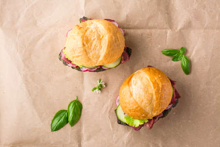 Ready-to-eat hamburgers with pastrami, cucumber, radish and herb on craft paper. American fast food. Top view