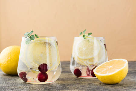 Summer refreshing cold cocktail with lemon and cherry - hard seltzer in glasses on the table
