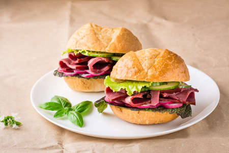 Ready-to-eat hamburgers with pastrami, vegetables and basil on a plate on craft paper. American fast food