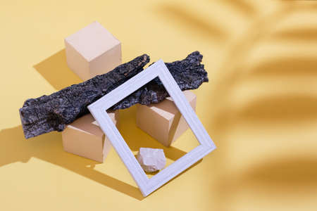 Modern abstract life style background: yellow cardboard, blank photo frame, stones, tree bark and shadow from a branch with leaves. Place for text