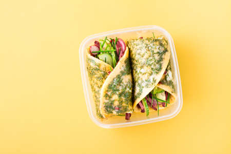 Egg rolls filled with pastrami, vegetables and green onions in a box on a yellow background. Takeaway, school breakfast Standard-Bild