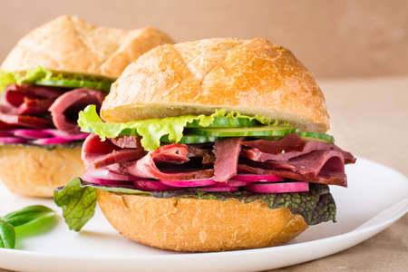 Ready-to-eat hamburger with pastrami, vegetables and basil on a plate on craft paper. American fast food. Close-up Standard-Bild
