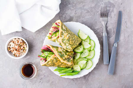 Egg rolls filled with pastrami, vegetables and green onions on a plate, sprouted grains and soy sauce in bowls on the table. Hearty and high-calorie snack. Top view