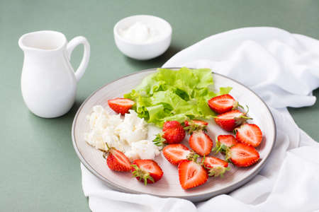 Fresh whole and sliced strawberries, cottage cheese and lettuce on a plate and sour cream in a bowl on a green background. Summer vitamin snack