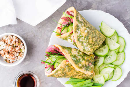 Egg rolls filled with pastrami, vegetables and green onions on a plate, sprouted grains and soy sauce in bowls on the table. Hearty and high-calorie snack. Top view. Close-up Standard-Bild