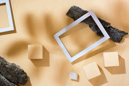Modern abstract life style background: concrete, blank photo frames, stones and tree bark in the shadows of the leaves. Top view. Place for text