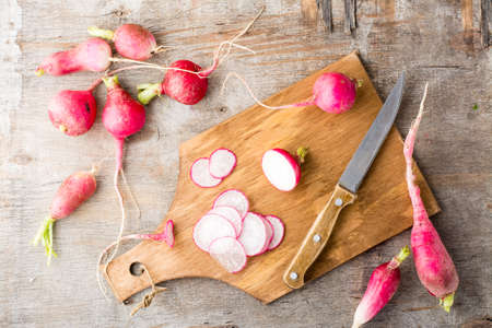 Fresh chopped radishes and a knife on a cutting board on a wooden table. Vegetables for a vegetarian diet. Rustic style. Top view