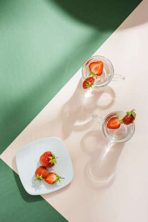 Infused water with strawberries in glasses and berries on a saucer on a green-pink background in hard light with shadows. Detox drink. Vertical and top view. Copy space