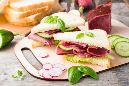 Fresh white bread sandwiches with pastrami, cucumber, radish and basil on a cutting board. American snack. Rustic style Standard-Bild