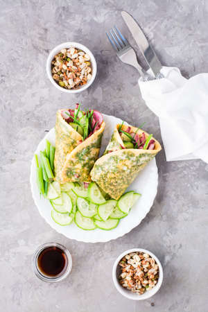 Egg rolls filled with pastrami, vegetables and green onions on a plate, sprouted grains and soy sauce in bowls on the table. Hearty and high-calorie snack. Top and vertical view Standard-Bild