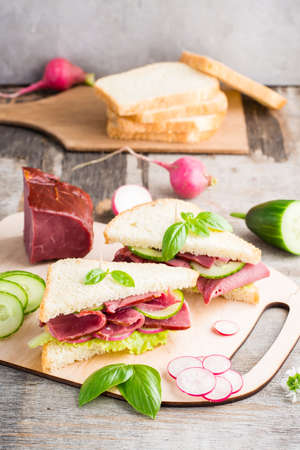 Fresh sandwiches with pastrami and vegetables on a cutting board. American snack. Rustic style. Vertical view