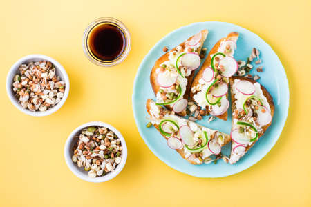 Ready-to-eat bruschetta with curd cheese, vegetables and sprouted grains on a plate on a yellow background. Healthy snacks. Top view