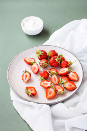Fresh whole and sliced strawberries on a plate and sour cream in a bowl on a green background. Summer vitamin food. Vertical view