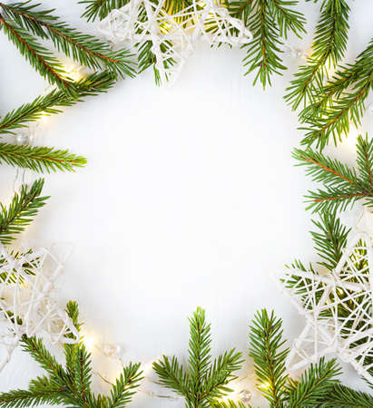 Christmas lights garland circular border and fir branches and white stars with copy space. Zdjęcie Seryjne