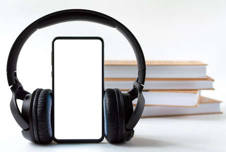 phone and headphones in the background of books. concept choice of technology or classics