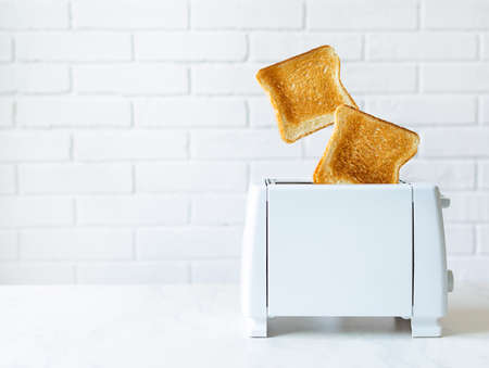 Roasted toast bread popping up of toaster with white brickwall