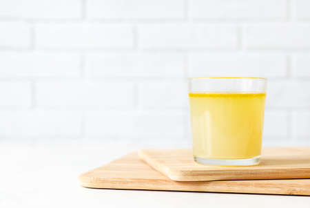 Delicious homemade chicken broth in a glass cup on white background