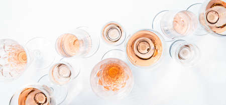 Sparkling rose wine in different glasses on white background.