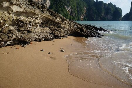Photo of a sandy deserted beach by the sea. Coastal cliffs. Tropical landscape background.