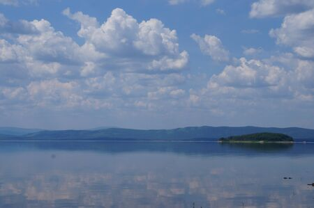 Photo of a lake and white cumulus clouds reflected in the water. Natural landscape background.